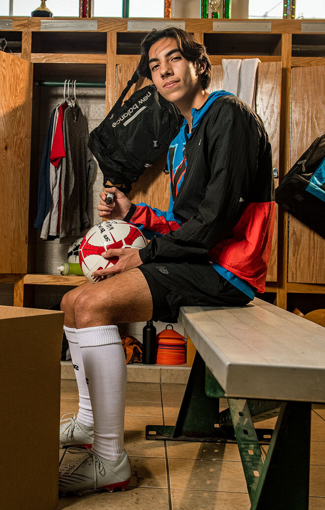 A teenage boy sitting in a football locker room wearing an NB Impact Run Light Pack Jacket as he writes on a football to send to professional footballer and NB athlete, Sadio Mané