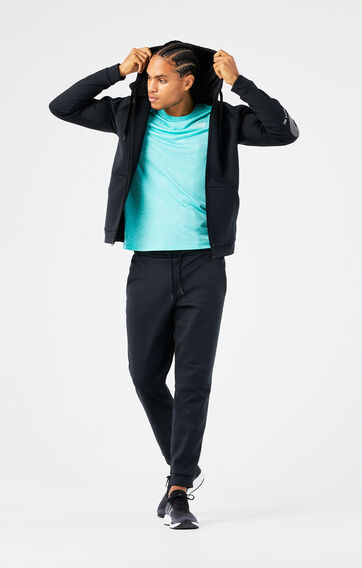 Man holding his hood up and wearing a blue shirt with a black hoodie and black sweatpants from the Tenacity Collection