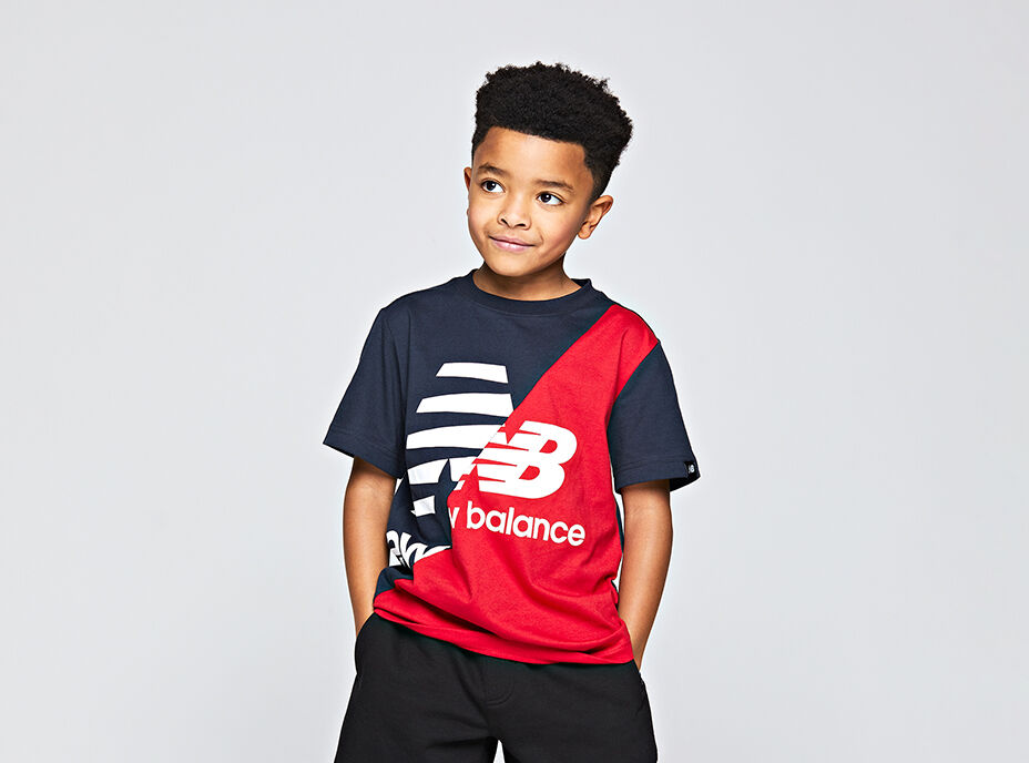 Waist-up crop of a young boy wearing a navy-blue and red NB Lifestyle Splice tee with black shorts