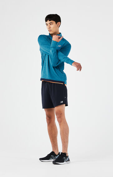 Man stretching wearing a blue long sleeve, half-zip pullover with black shorts and running shoes