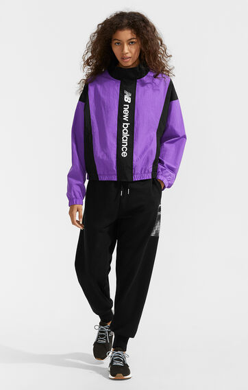 Standing woman wearing a purple & black NB jacket, black NB sweatpants, and black & grey NB Fresh Foam Roav shoes