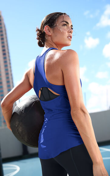 Woman wearing red workout tank holding a medicine ball
