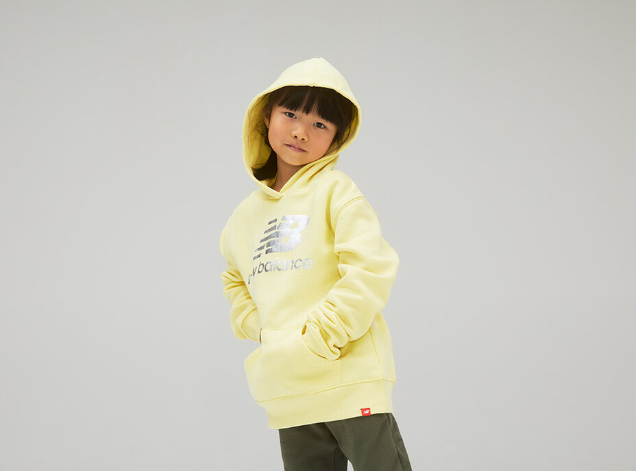 Kid wearing an all yellow hoodie with the hood on her head.