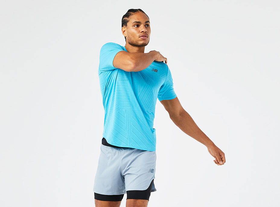 Man stretching wearing a blue short sleeve shirt