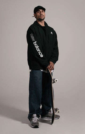 Tiago Lemos standing against grey studio backdrop holding his skateboard while wearing grey NB apparel and shoes