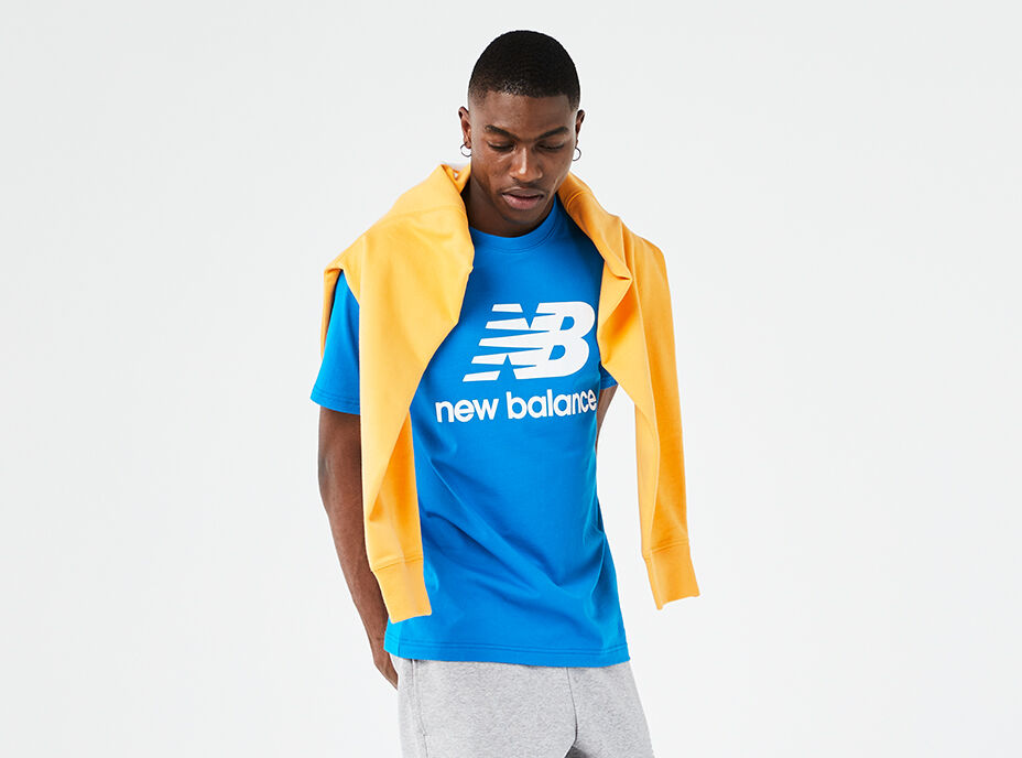 Man wearing a blue NB Essentials tee with grey sweatpants and a yellow sweatshirt draped over his shoulders