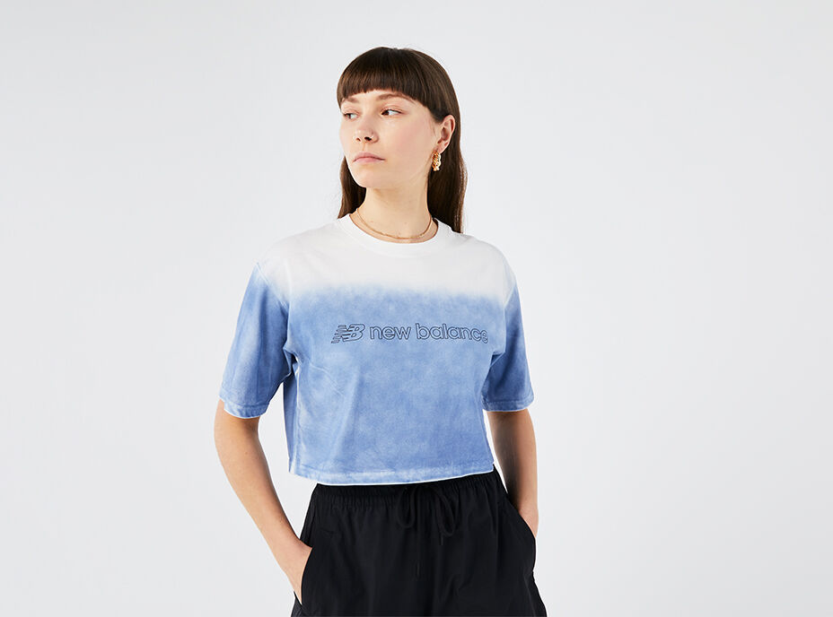 Waist-up crop of a woman wearing a light blue and white NB Sport Style Optiks Gradient Spray Tee with black pants