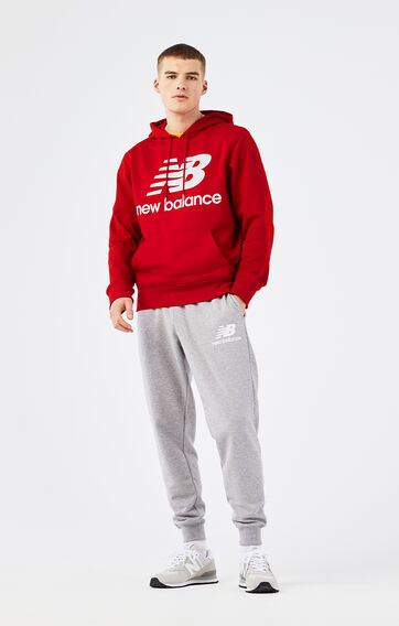 Man wearing a NB Essentials red hoodie and grey sweatpants