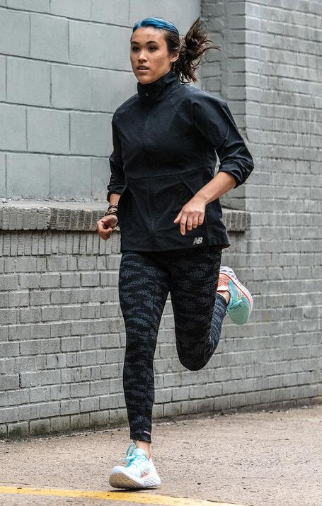 Woman running on sidewalk wearing a black NB jacket, black NB tights, and light blue NB Fresh Foam 1080v10 shoes, NIQUAN ENERGY TRINIDAD LTD VACANCY