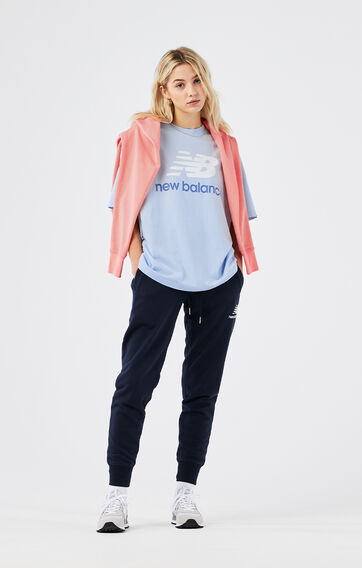 A woman wearing a blue NB Essentials tee with navy blue sweatpants and a pink sweatshirt draped over her shoulders