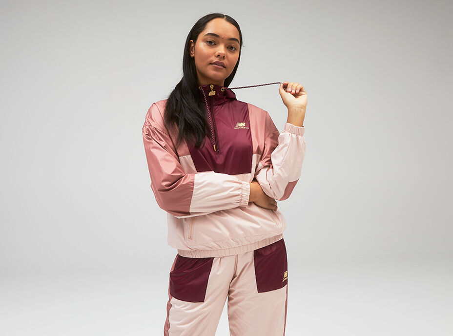 Young woman wearing pink and maroon track jacket while tugging on one of the hoodie strings.