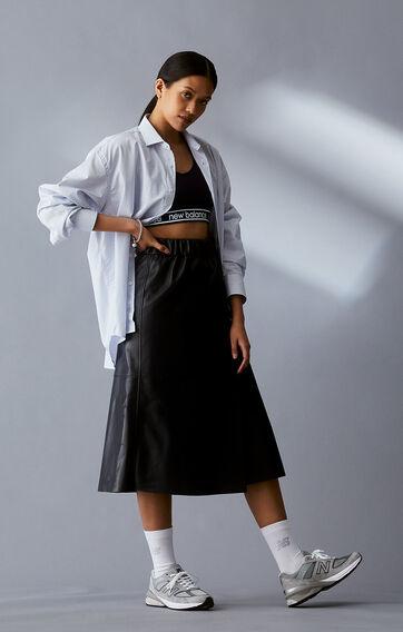Woman posing wearing a black NB sports bra, black skirt, and grey NB 990v5 sneakers