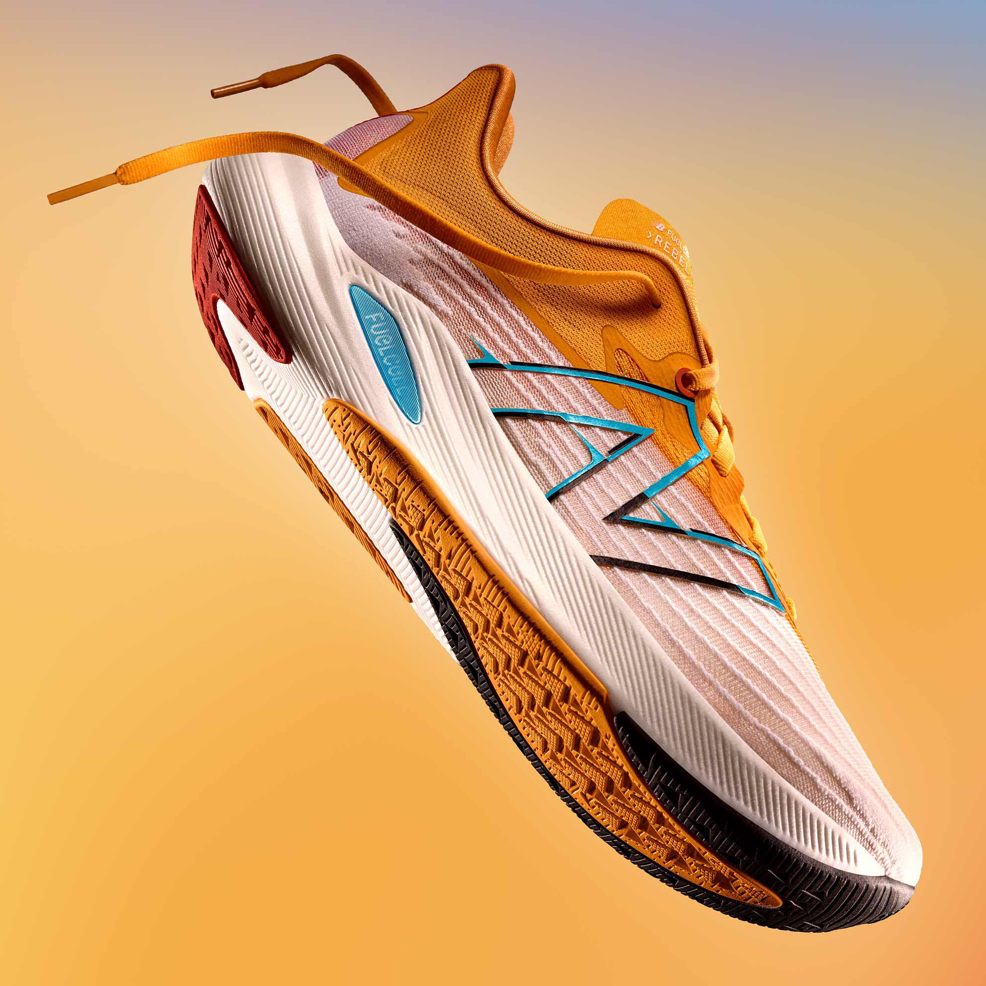 A dramatically lit men's orange and white NB FuelCell Rebel v2 running shoe on a warm gradient background