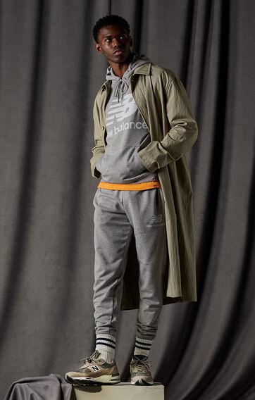 Man posing wearing a grey NB Essentials hoodie, grey NB Essentials joggers, and warm grey NB 991 sneakers